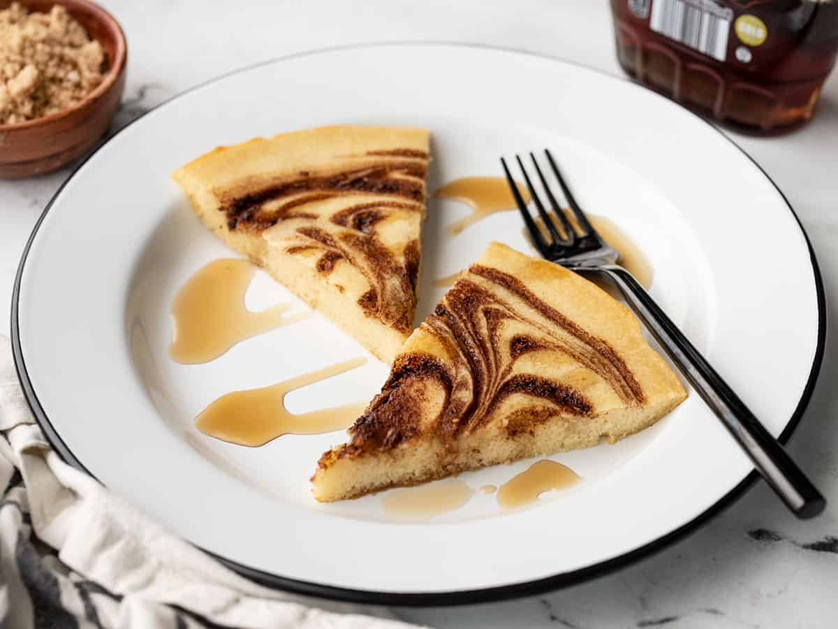 front view of two slices of oven pancake on a plate with maple syrup and a fork