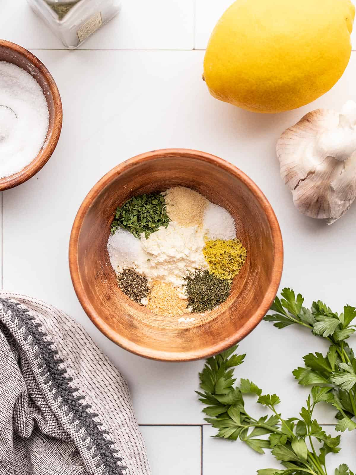Ranch seasoning mix ingredients in a small wooden bowl with lemon, garlic, and parsley on the sides