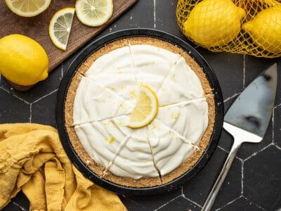 Overhead view of a sliced lemon cream pie with lemons on the sides