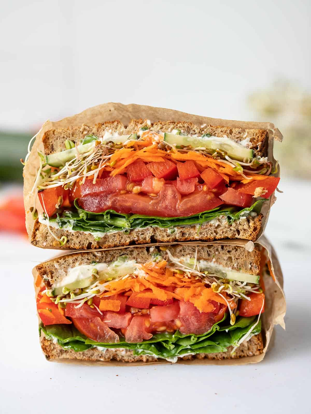 An ultimate veggie sandwich cut in half and stacked, cut sides facing the camera