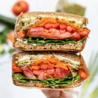 A hand holding both halves of a cut open ultimate veggie sandwich