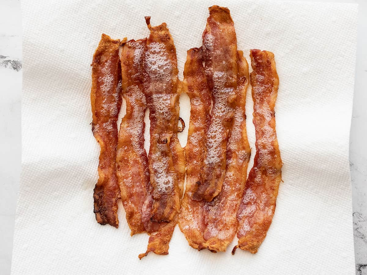 cooked bacon strips on a paper towel lined plate