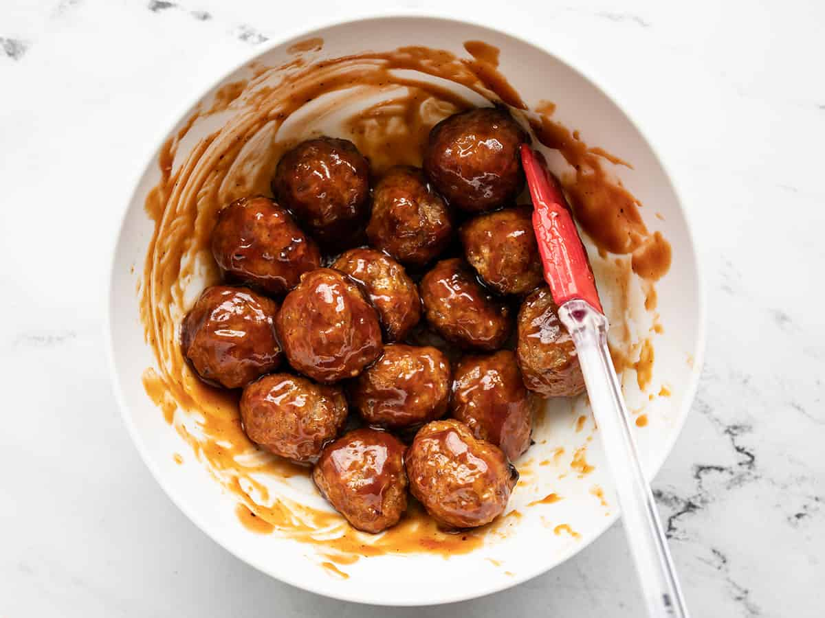 BBQ sauce coated meatballs in a bowl with a spatula