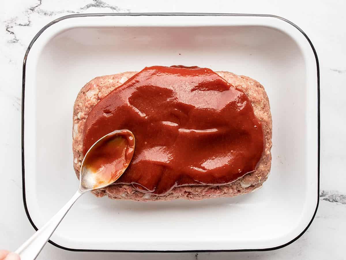 Glaze being spread over the meatloaf