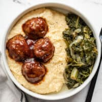 Overhead view of a bowl of cheese grits with bbq meatballs and collard greens