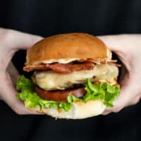 Close up side view of a ranch turkey burger held in hands