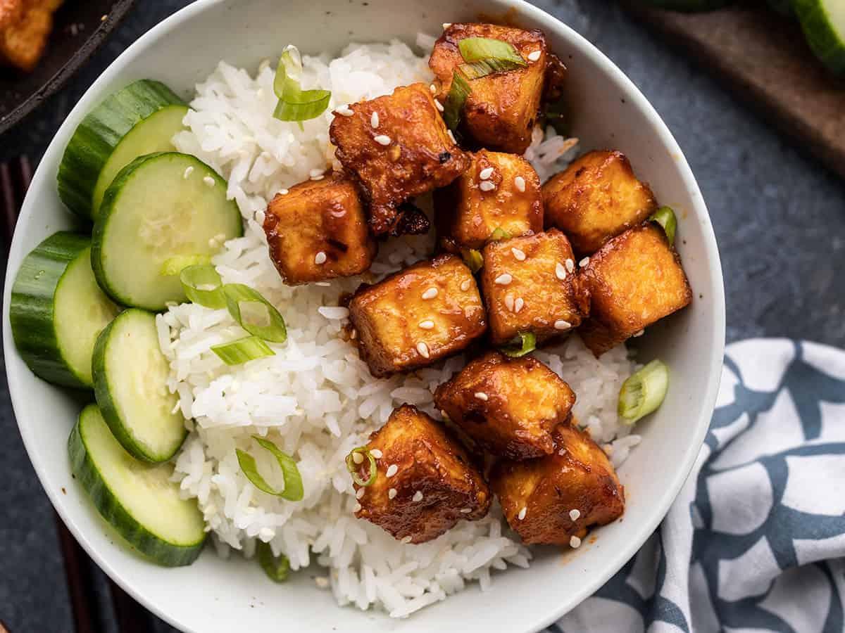close up of honey sriracha tofu in a bowl with cucumber