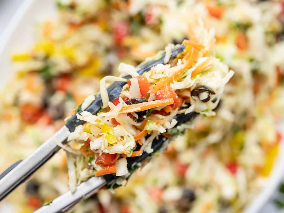 Close up of mediterranean coleslaw in tongs with the serving dish in the background