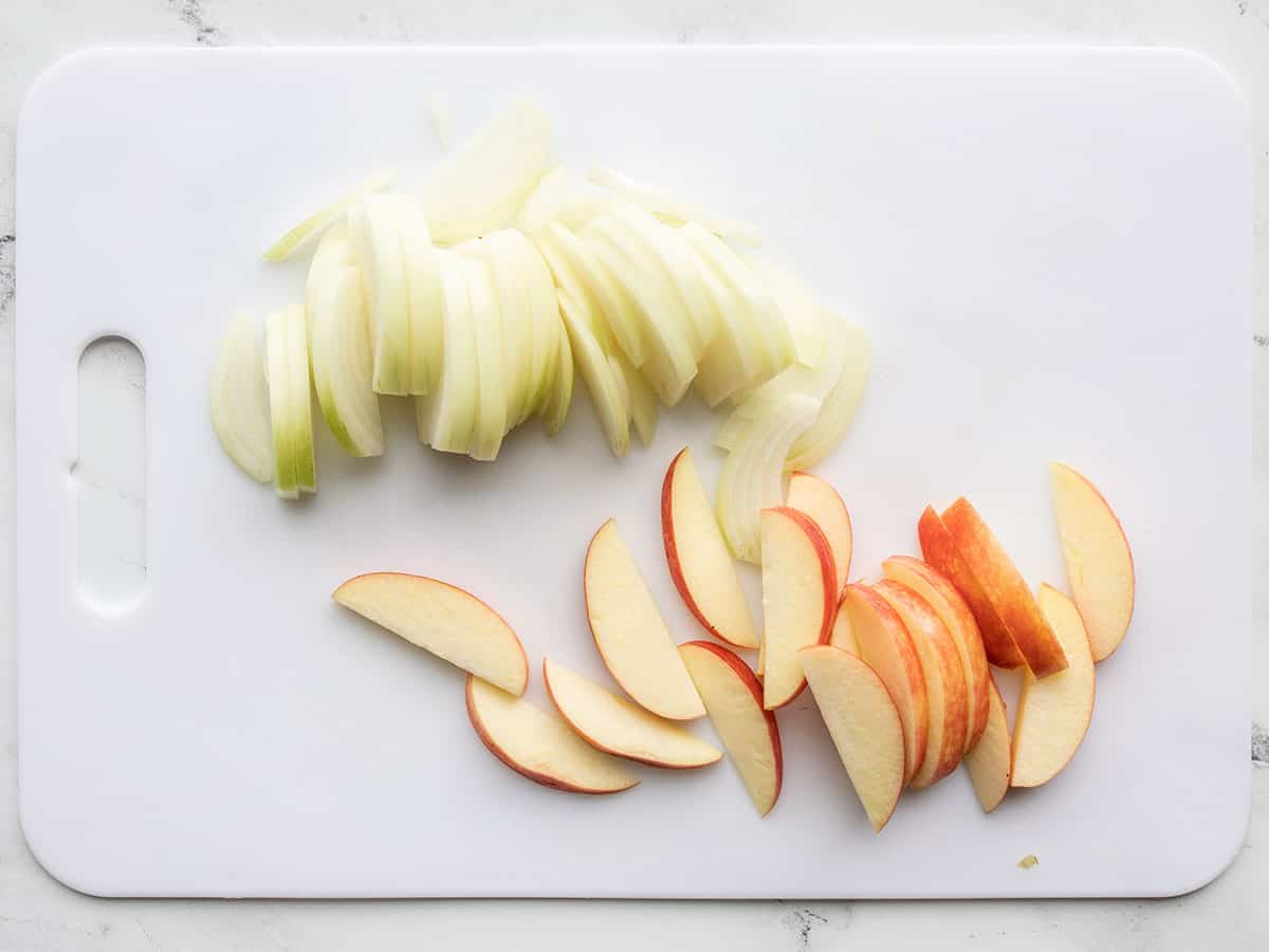Sliced onion and apple on a cutting board