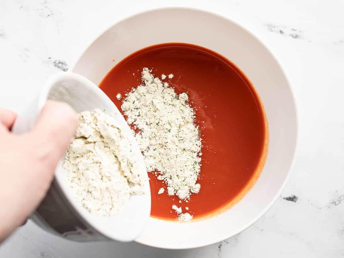 ranch seasoning being poured into a bowl of hot sauce