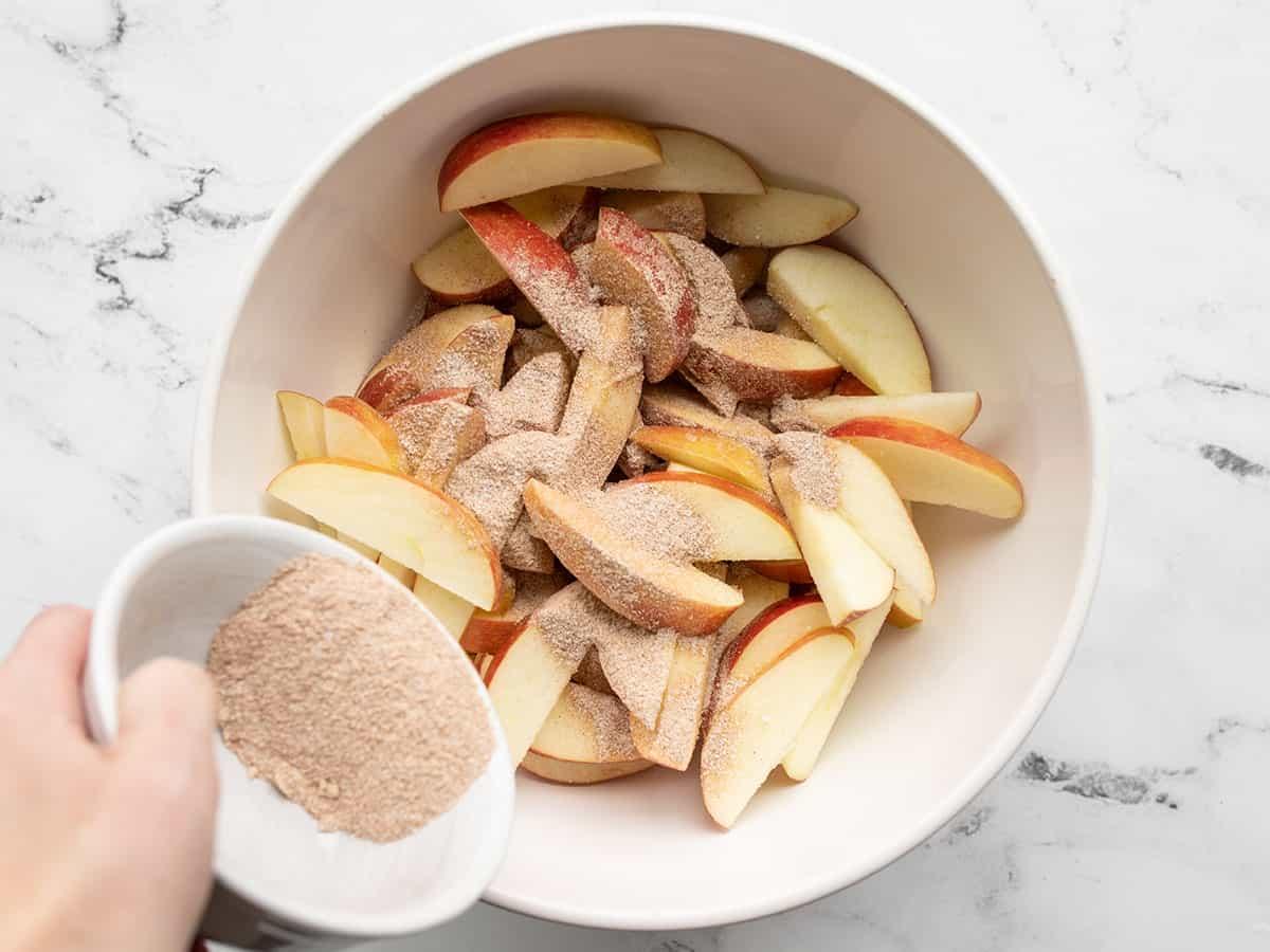 Seasoning being sprinkled over the apples