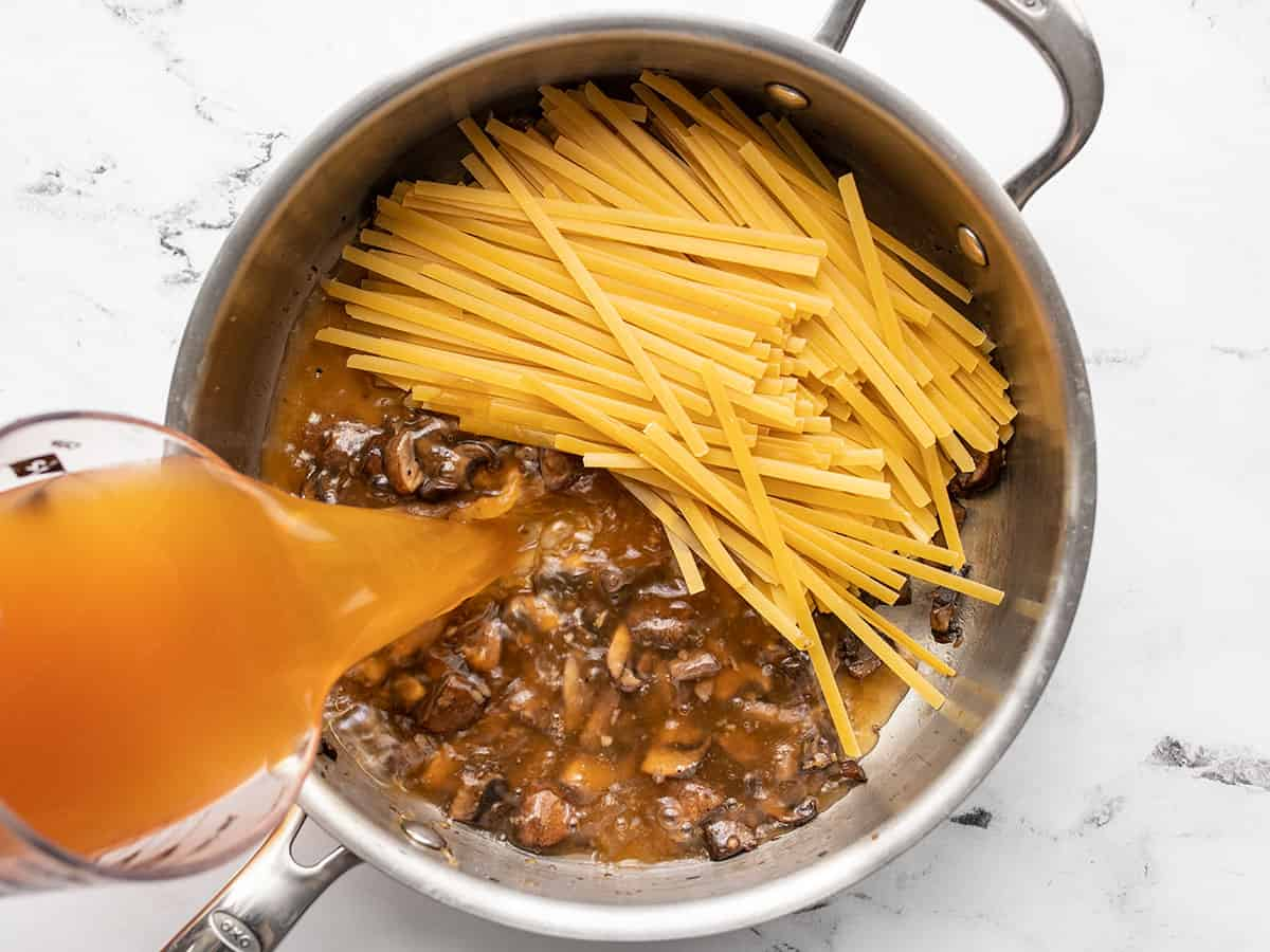 fettuccine in the skillet, broth being poured in