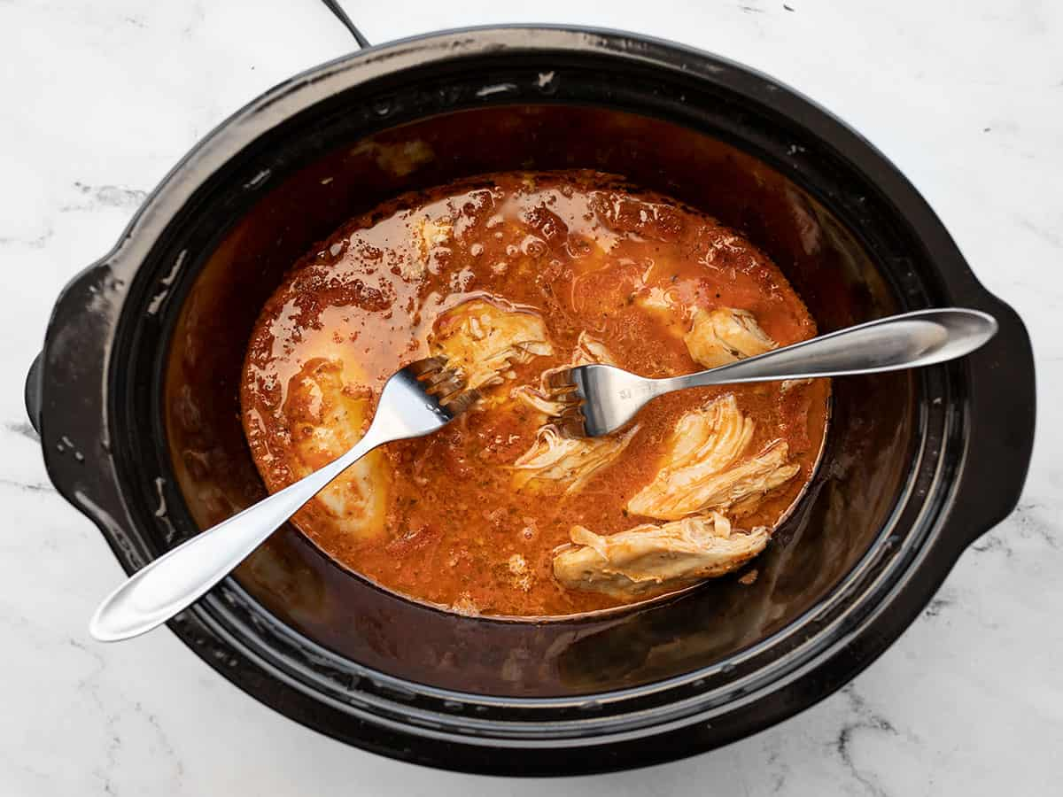 two forks shredding the chicken in the slow cooker