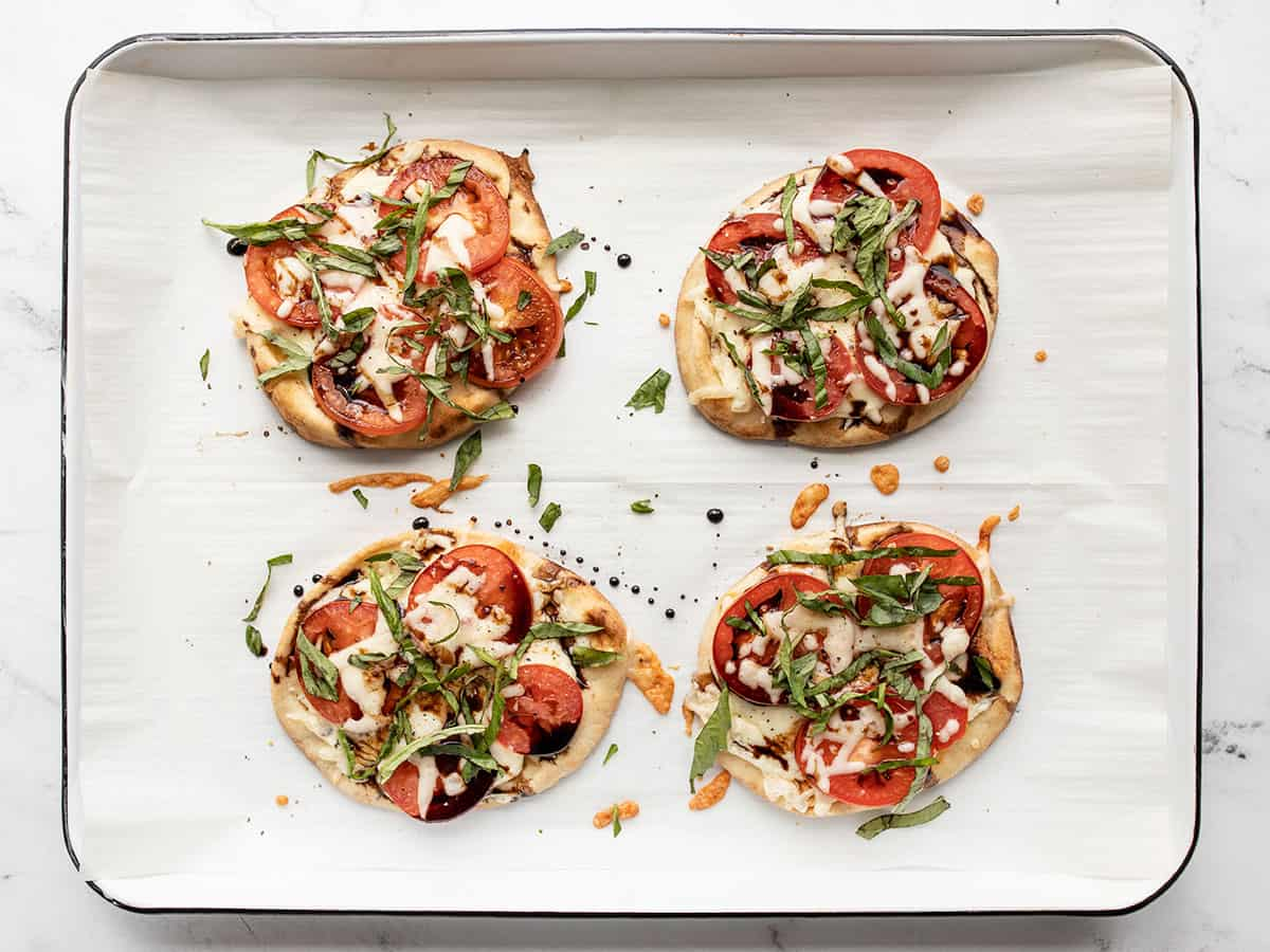 finished caprese pizzas topped with fresh basil
