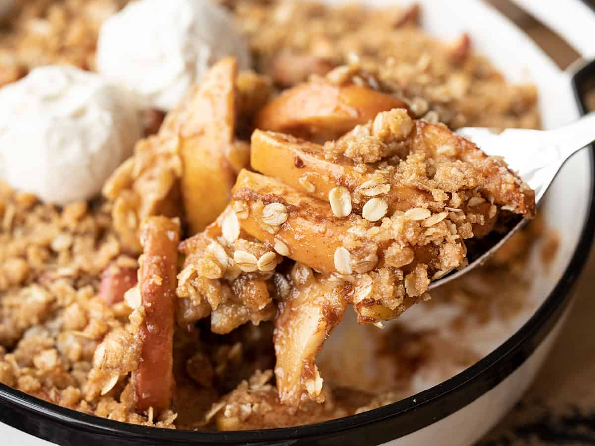 close up of apple crisp being scooped out of the baking dish