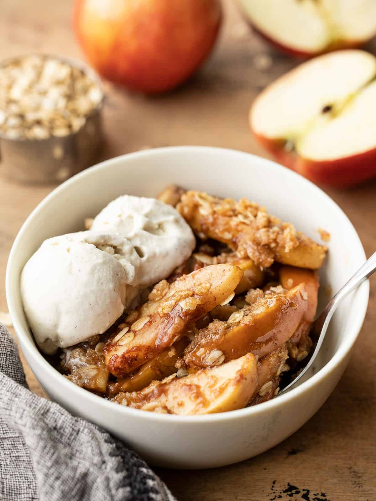 apple crisp in a bowl topped with ice cream