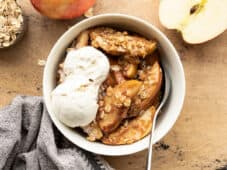 Apple crisp in a bowl topped with vanilla ice cream