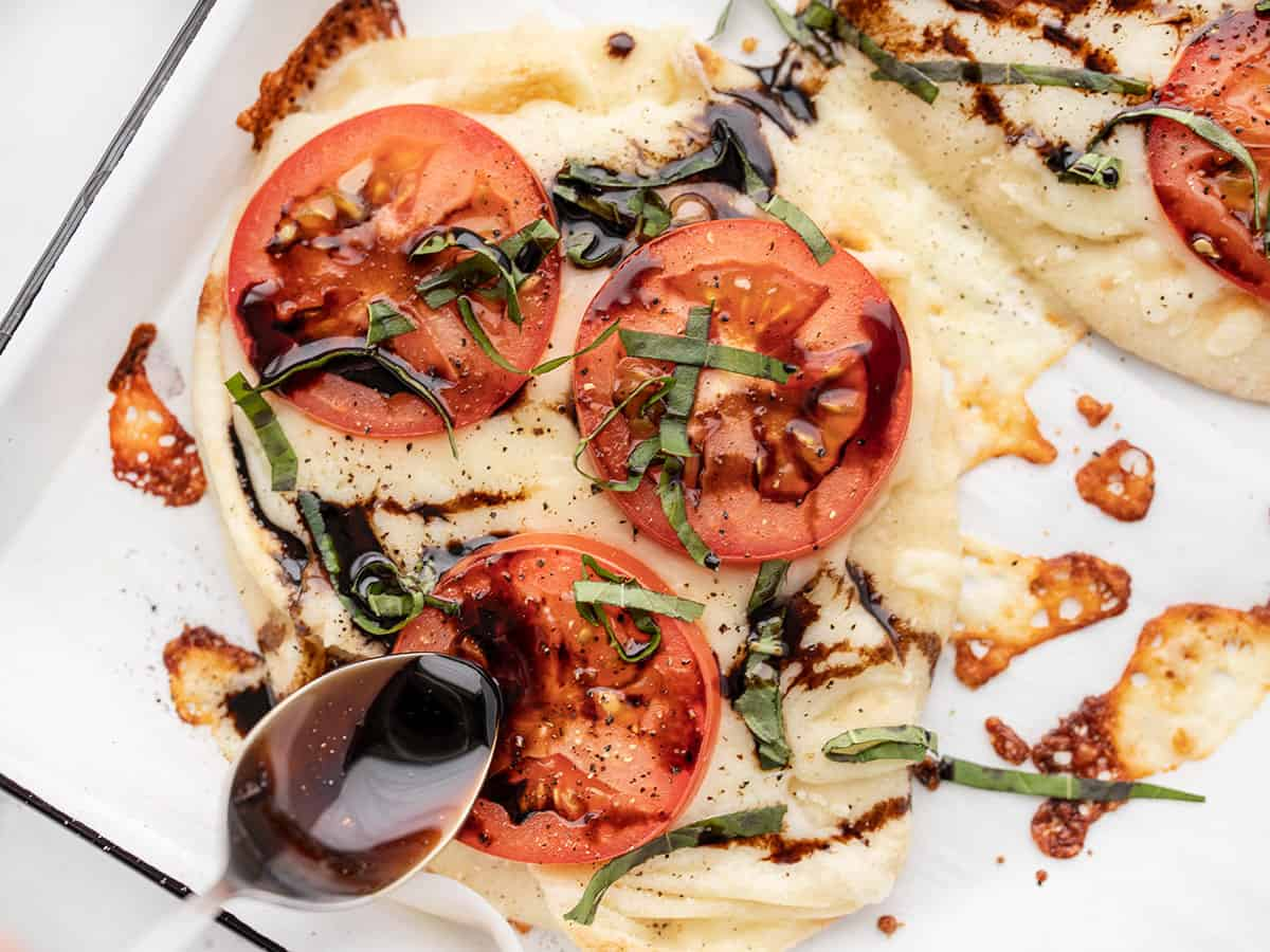 Balsamic glaze being drizzled over a Caprese pizza close up