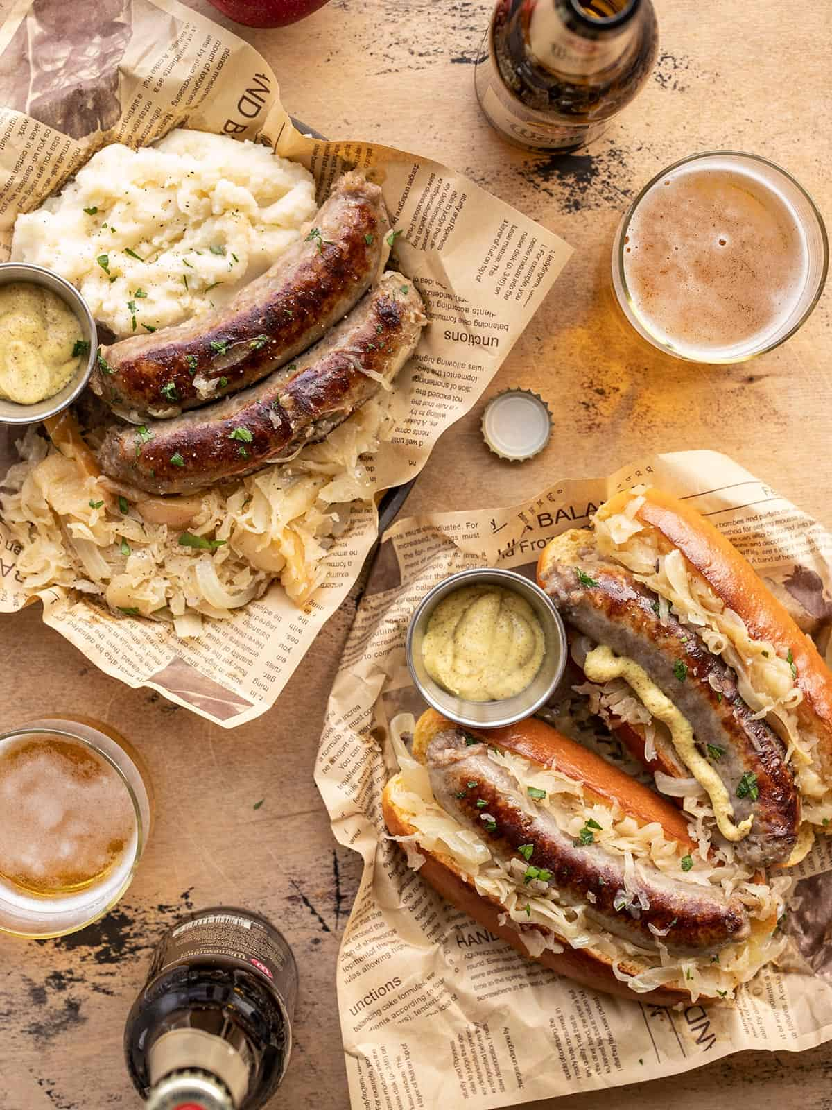 Bratwurst and Sauerkraut on two plates, one with buns and one with mashed potatoes