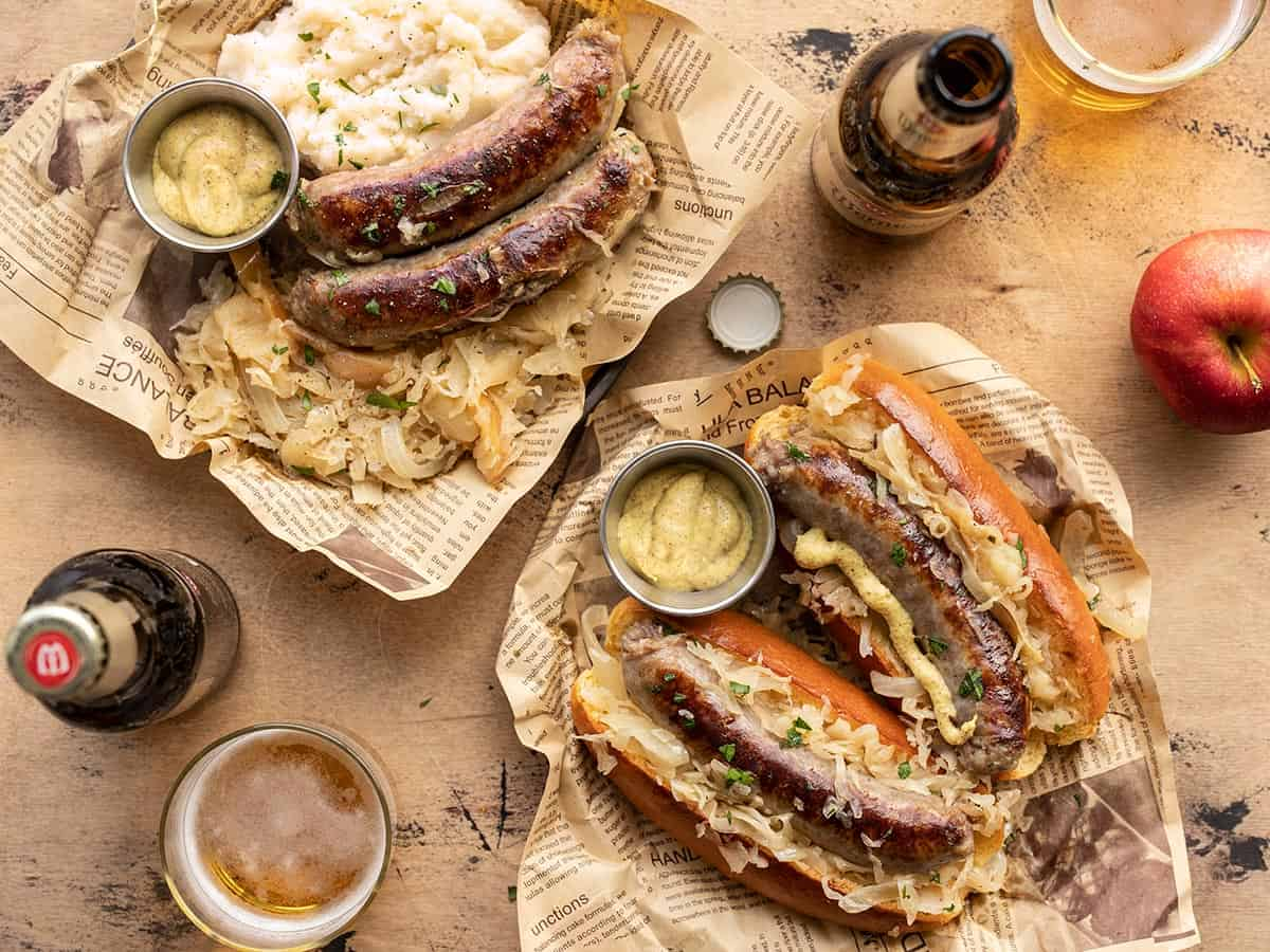 bratwurst and sauerkraut on plates with beer on the sides