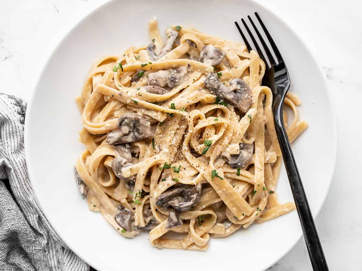 Overhead view of creamy mushroom pasta on a plate with a fork