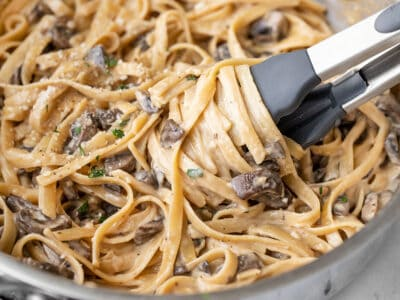 Close up of pasta being twirled around the tongs in the skillet