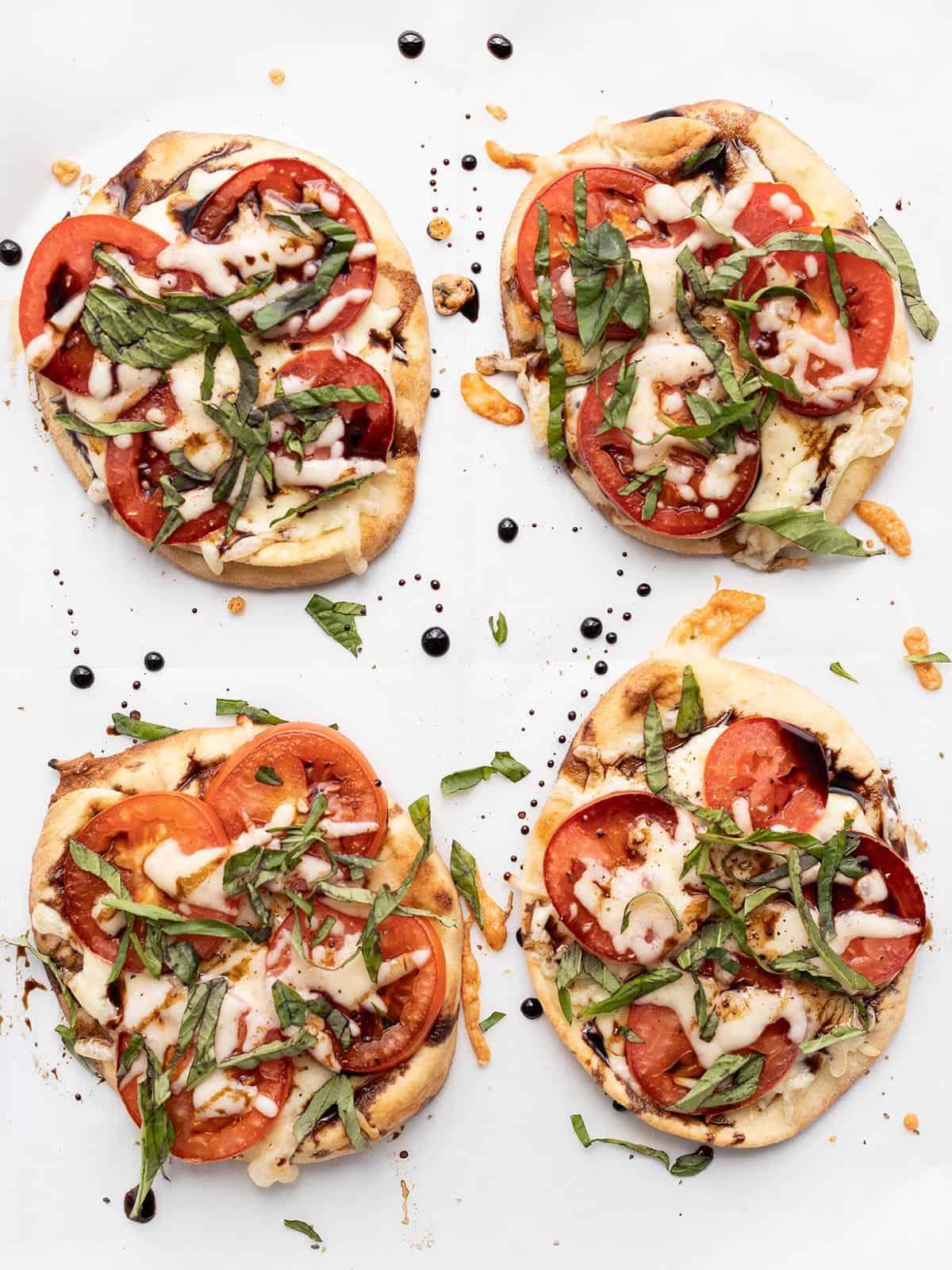 four mini caprese pizzas on a baking sheet