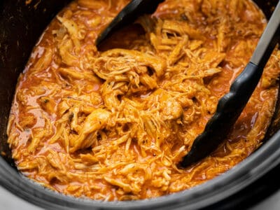 Close up side view of shredded buffalo chicken in the slow cooker with tongs