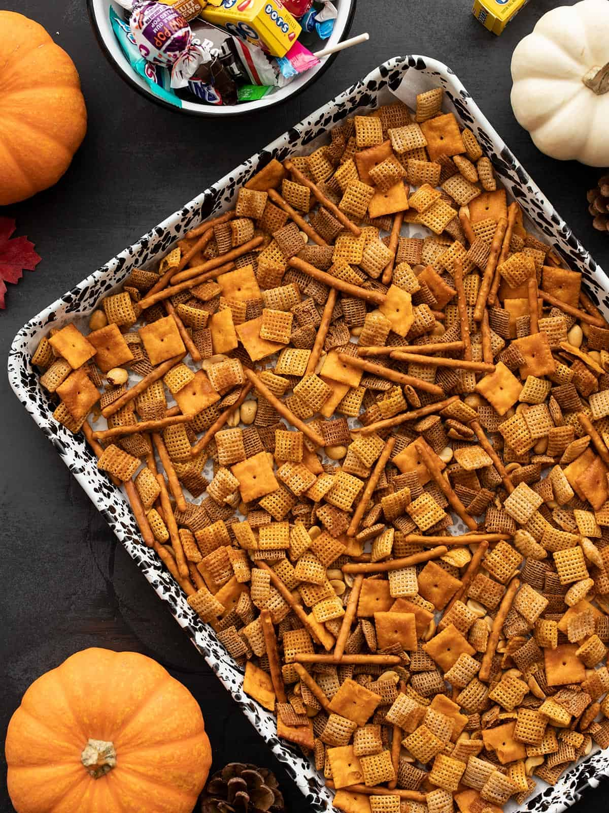Spicy chex mix on a baking sheet with fall ornaments on the sides