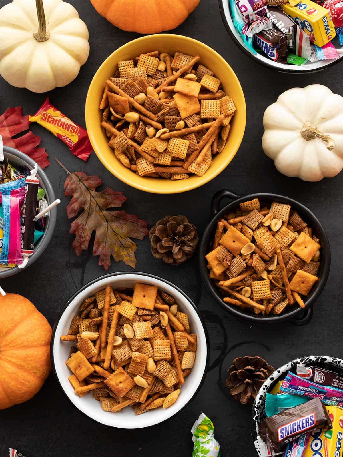 Three bowls of chex mix next to bowls of candy and pumpkins