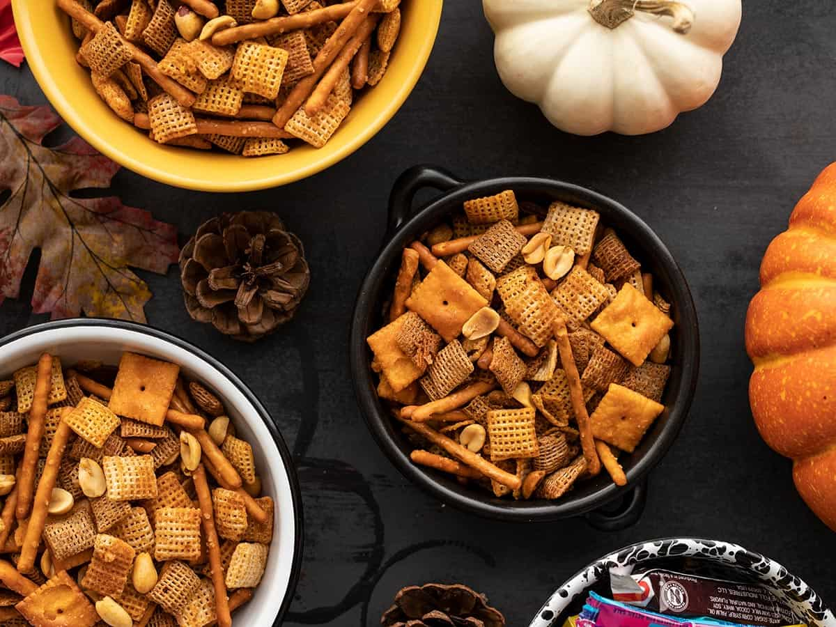 Three bowls of spicy chex mix with pumpkins on the sides